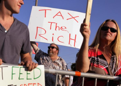 124752354-craig-glaser-holds-a-sign-reading-tax-the-rich-outside.jpg.CROP.promo-mediumlarge
